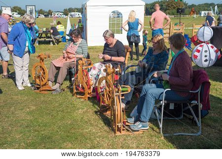 DENEKAMP NETHERLANDS - SEPTEMBER 25 2016: elderly women working on wooden spinning wheels during a festival
