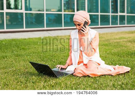 Young Muslim Woman Using Mobile Phone and Laptop In Park.