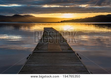 The summer sun rising over the hills on Loch Lomond Scotland