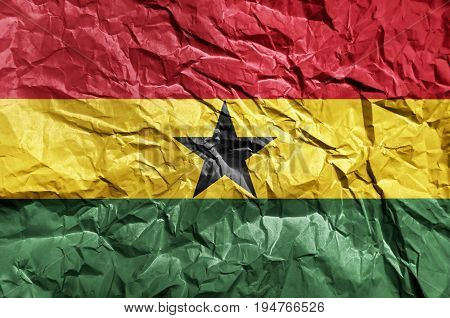 Ghana flag painted on crumpled paper background