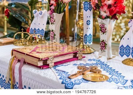 Golden crowns and Scripture on altar in church during wedding ceremony