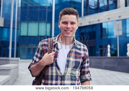 Close-up shot of happy man listening to music in front of business canter. Urban city concept, using headphones