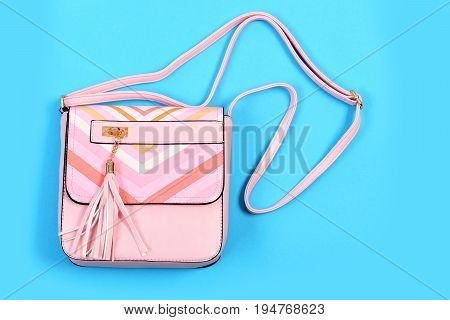 Purse in light pink color with stripes. Handbag for women isolated on cyan blue background. Accessory in modern style made of leather. Fashion and glamour concept poster