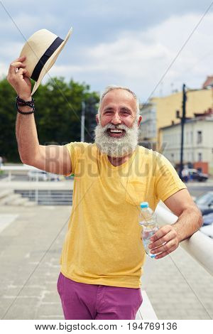 Mid shot of smiley bearded man taking off hat while standing with bottle of water