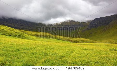 Green grass and mountains a cloudy day at Faroe Islands, Danmark. Rainy day in july.