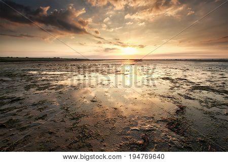 sunset over Wadden sea coast Friesland Netherlands