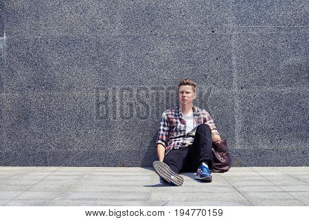 Mid shot of relaxed student having rest and listening to music outdoors. Wearing casual clothes, listening to music