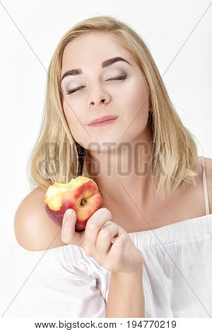Portrait of  beautiful blond woman with pleasure eating nectarine