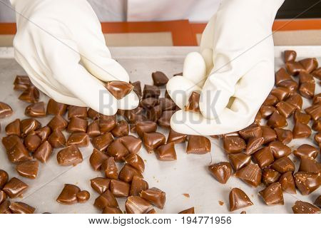 Artisanal production of caramel toffee sweets butterscotch candies. Woman with white lab coat blouse shaking separating removing the pieces of butterscotch candies traditional sweets of France