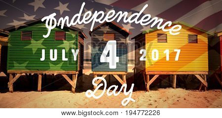 Digitally generated image of happy 4th of july message against colorful huts on sand at beach