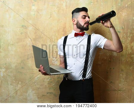 Man In White Shirt Drinks Wine And Holds Laptop