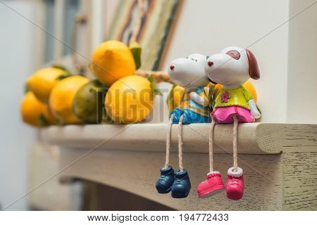 Close up two small figurines of happy dogs sit on shelf. Love concept