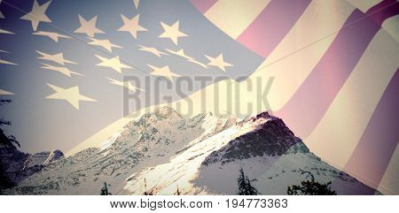 Close up of the us flag against scenic view of snow covered mountains