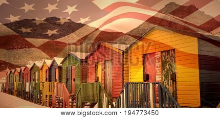 Focus on usa FLAG against multi colored wooden huts by mountain at beach