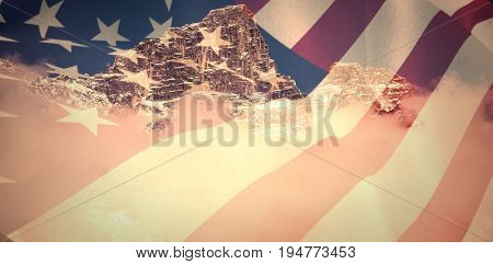 Close up of the us flag against view of snowy mountain range and clouds