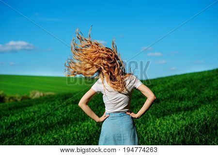 Young Beautiful Woman Is Shaking Her Hair On Greenfield From The Back