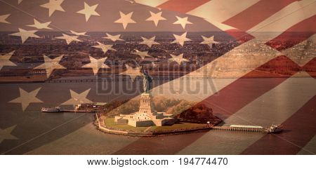 Close up of the us flag against high angle view of statue of liberty in sea