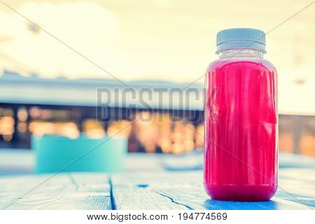Close up soft fruit strawberry drink in plastic bottle on wooden table in outdoors restaurant