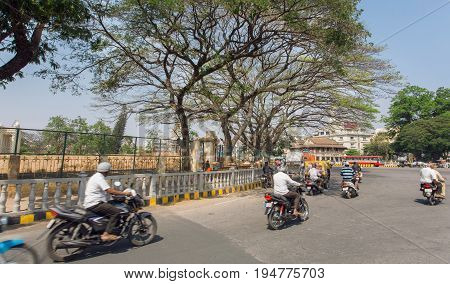 MYSORE, INDIA - FEB 17, 2017: Speeding motorcycles under trees of the old streets of indian city on February 17, 2017. Mysore of Karnataka has a population of 900000