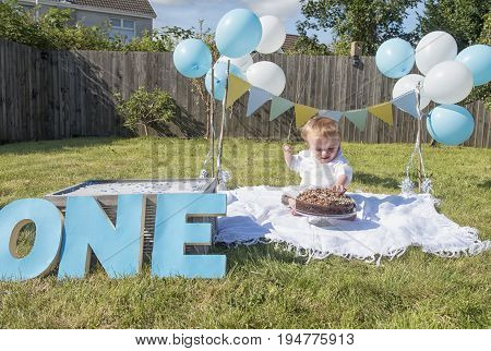 One year old baby boy chocolate cake smash outdoors