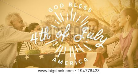 Digitally generated image of happy 4th of july message against happy family having a picnic and making a toast