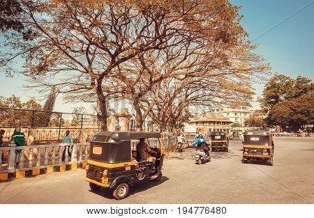 MYSORE, INDIA - FEB 17, 2017: Auto rickshaw driving on traffic street of indian city on February 17, 2017. Mysore of Karnataka has a population of 900000