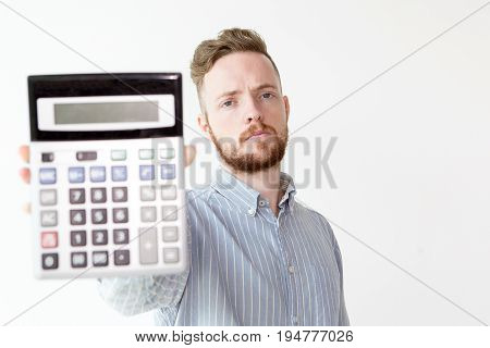 Portrait of serious bearded young Caucasian businessman wearing shirt stretching hand with calculator and showing economy of deal