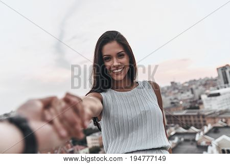 I will never let you go! Beautiful young woman smiling and looking at camera while holding hands with her boyfriend outdoors