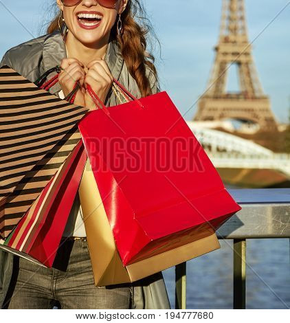 Get your bags ready for the Paris autumn sales. Closeup on cheerful young elegant woman in trench coat with shopping bags near Eiffel tower