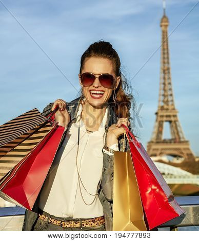 Get your bags ready for the Paris autumn sales. Portrait of happy young trendy woman in trench coat with shopping bags near Eiffel tower