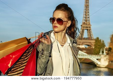 Get your bags ready for the Paris autumn sales. young elegant woman in trench coat with shopping bags in Paris France looking into the distance