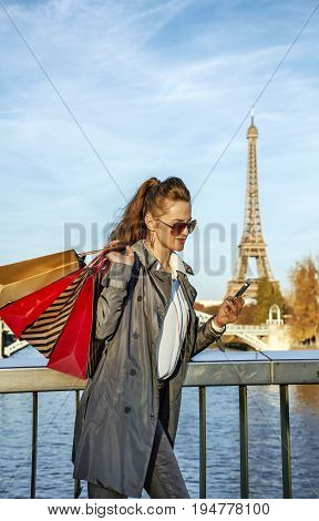 Get your bags ready for the Paris autumn sales. smiling young trendy woman in trench coat with shopping bags writing sms near Eiffel tower