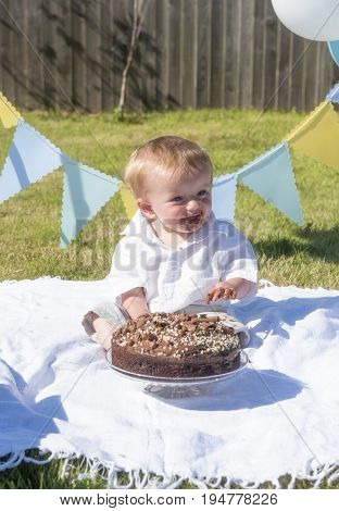 Vertical image of a one year old baby boy chocolate cake smash