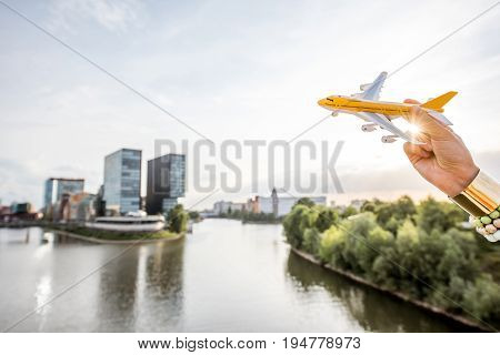 Flying with toy airplane on the modern city background in Dusseldorf, Germany. Air transportaion connection in Germany concept
