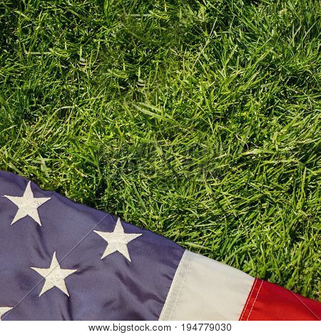 Creased US flag against grass background