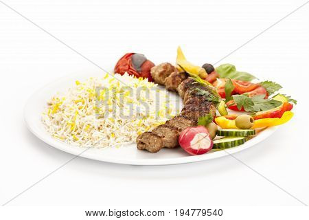 Crispy grilled lamb kebab taken off the skewer and served on a plain plate. Low angle view studio shot. Closeup. Barbecue meal fusion food concept Persian traditional dish or hearty eating.
