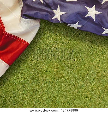 Creased US flag against green background