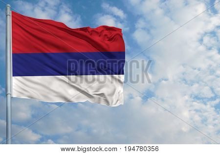 National flag of Republika Srpska on a flagpole in front of blue sky.