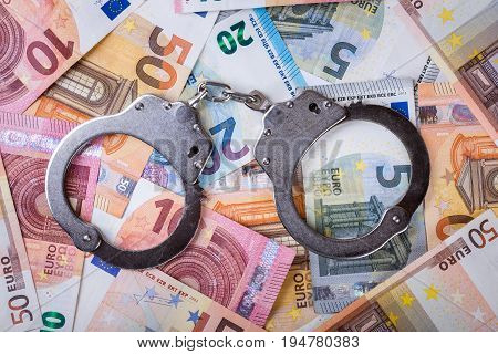 dirty money and corruption concept - handcuffs with euro bills