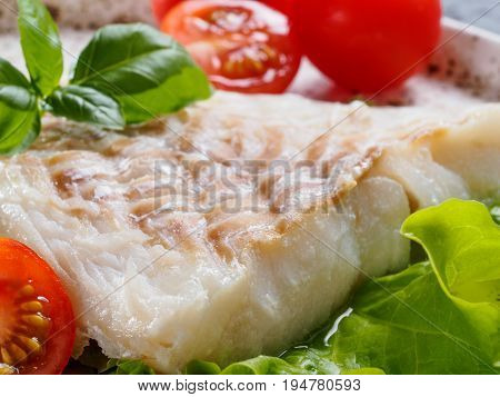 Close up view of grilled codfish with basil and cherry tomatoes in trendy white plate.
