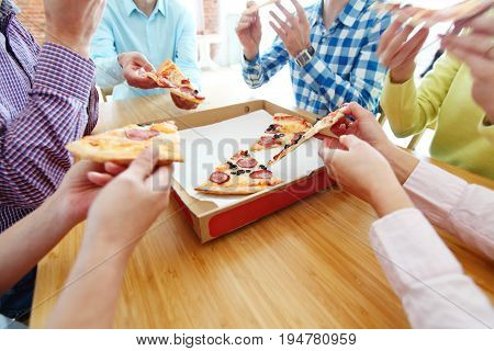 People hands grabbing pizza from delivery box closeup