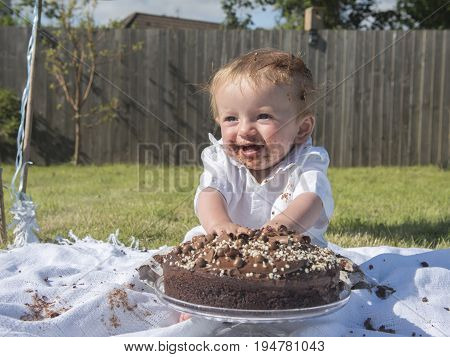 Happy one year old baby boy chocolate cake smash