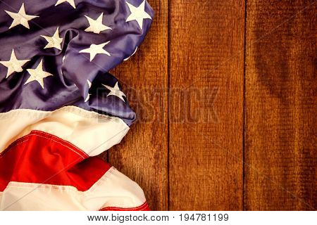 Creased US flag against wooden background