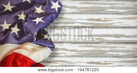 Creased US flag against wood background