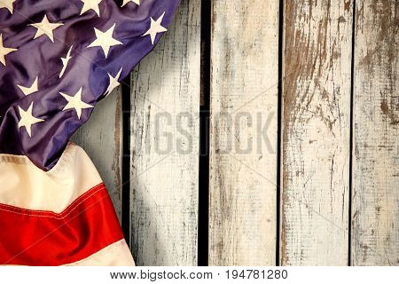 Creased US flag against wood panelling in pattern