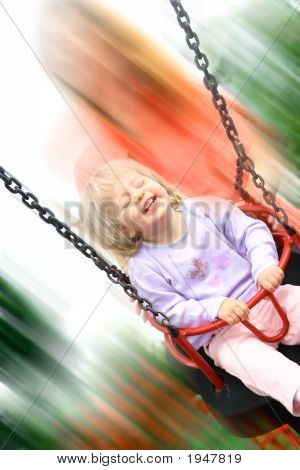Toddler Girl Enjoying A Fast Ride On Swing