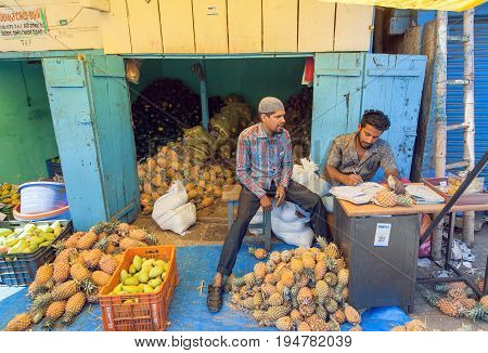 MYSORE, INDIA - FEB 16, 2017: Young businessmen traders of pineapples and oranges on market of indian city on February 16, 2017. Mysore of Karnataka has a population of 900000