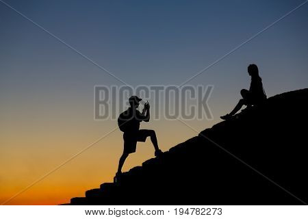 Silhouettes of young man and girl on the steps against a sunset background. Guy takes picture of girl on the phone.