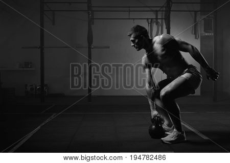 Young muscular man doing exercises with kettlebell in gym. Weightlifting workout. Sports, fitness concept. Black and white image. poster