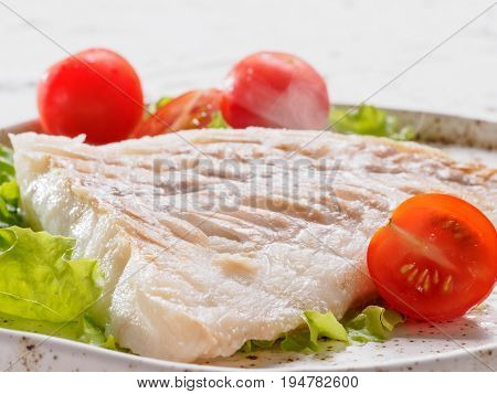 Close up view of hot grilled codfish with basil and cherry tomatoes in trendy white plate.